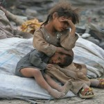 afghan girl holds her brother as they take a break from searching for items to recycle in kabul